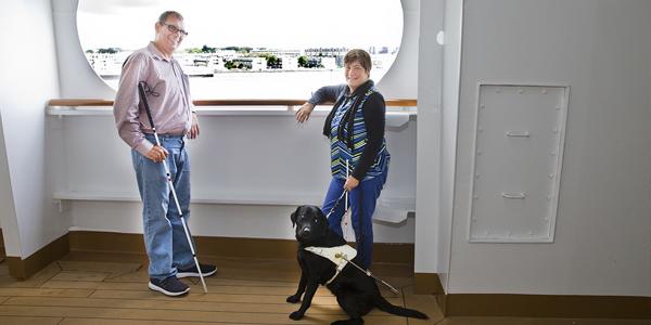 Conny en Corne met Joska op een boot voor een groot raam met uitzicht op het water